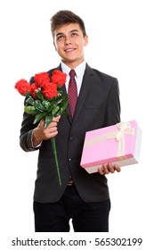 Thoughtful young happy businessman smiling while holding red roses and gift box ready for Valentine's day