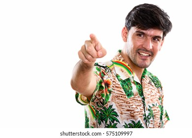 Thoughtful young happy Persian man smiling while pointing finger at distance