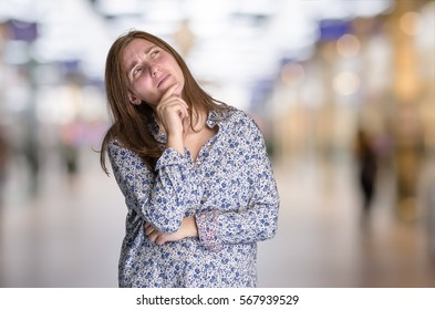 Thoughtful young hipster woman over blur  background.