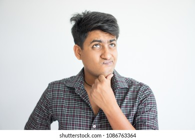 Thoughtful young Indian man touching chin. Contemplation concept. Isolated front view on grey background.