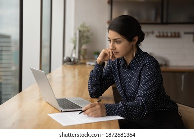 Thoughtful young Indian woman look at laptop screen working online in office. Pensive millennial ethnic female employee use computer watch webinar or training on gadget. Education concept.