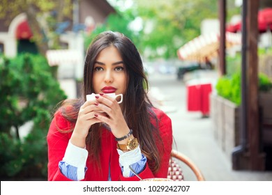 Thoughtful young indian woman thinking holding coffee on a trendy cafe terrace