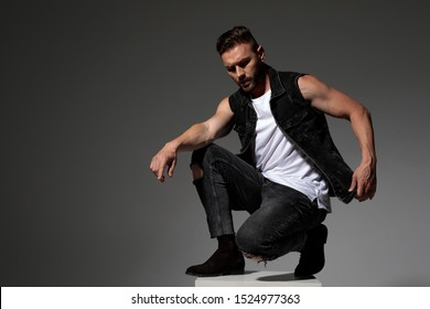 Thoughtful young man adjusting his jeans vest and squatting on a chair while wearing black jeans on gray studio background