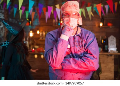 Thoughtful young man in a doctor costume celebrating halloween. Celebrating halloween in a night club.