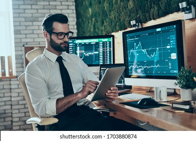 Thoughtful young man in formalwear working using digital tablet while sitting in the office