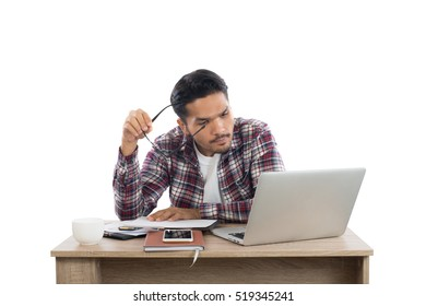 Thoughtful young man holding glasses looking at laptop while sitting at his working place.