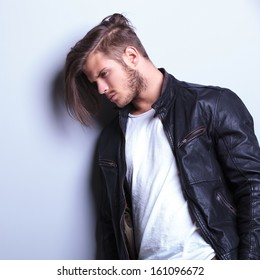 thoughtful young man in leather jacket, side view picture