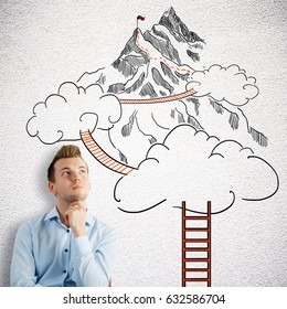 Thoughtful young man on concrete background with drawn ladder, clouds and way to mountain top. Success concept