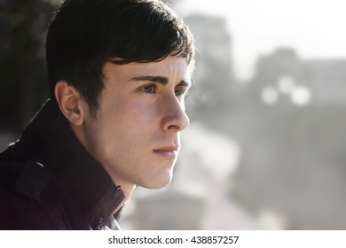 Thoughtful young man side portrait over clear landscape