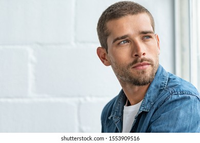 Thoughtful young man sitting near window and looking away. Handsome pensive guy lost in deep thoughts while looking outside the window. Closeup face of man in casual cloth contemplating, copy space.