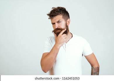 thoughtful young man standing by the wall. handsome bearded hipster man portrait with lush moustache and stylish hair on thoughtful face and white T-shirt touching long beard and thinking isolated.