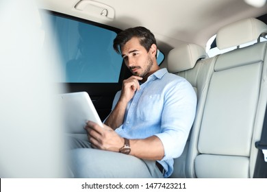 Thoughtful young man with tablet on backseat in luxury car