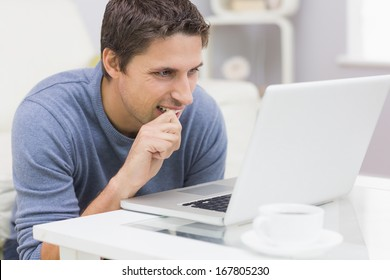 Thoughtful young man using laptop in the living room at home