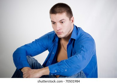 Thoughtful young man wearing an unbuttoned blue shirt and jeans (against a gray background)