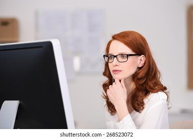 Thoughtful young redhead businesswoman wearing glasses reading her desktop monitor as she checks her work