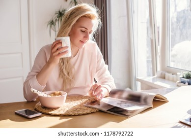 Thoughtful young woman in bathrobe eating breakfast in kitchen.