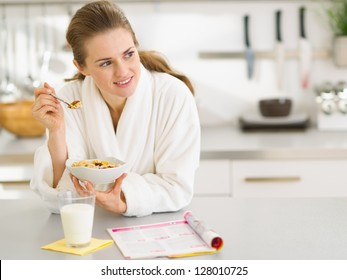 Thoughtful young woman in bathrobe eating breakfast in kitchen