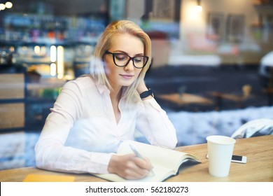 thoughtful young woman in a cafe taking notes during coffee break