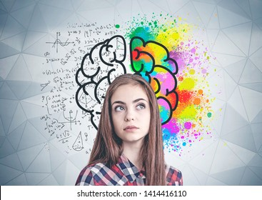 Thoughtful young woman in casual clothes standing near geometric pattern wall with colorful brain sketch drawn on it. Concept of creative thinking and science