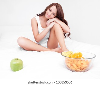 thoughtful young woman choosing between an apple and potato chips in bed at home