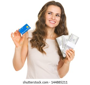 Thoughtful young woman with credit card and dollars looking on copy space