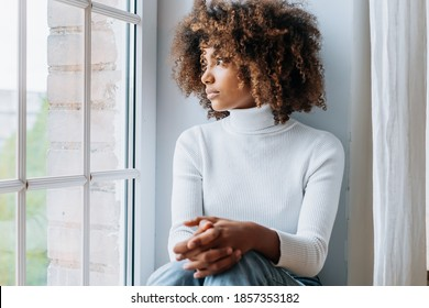 Thoughtful young woman with dark skin and modern kinky hair sits on white windowsill looking outside window close view