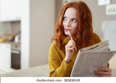 Thoughtful young woman doing a cryptic crossword puzzle in a newspaper looking off to the side with a pensive expression as she tries to solve a clue