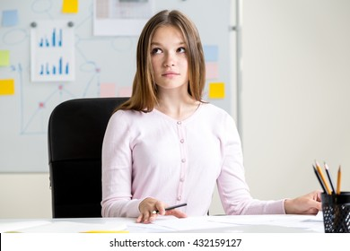 Thoughtful young woman doing paperwork at office desk with business charts on whiteboard in the background