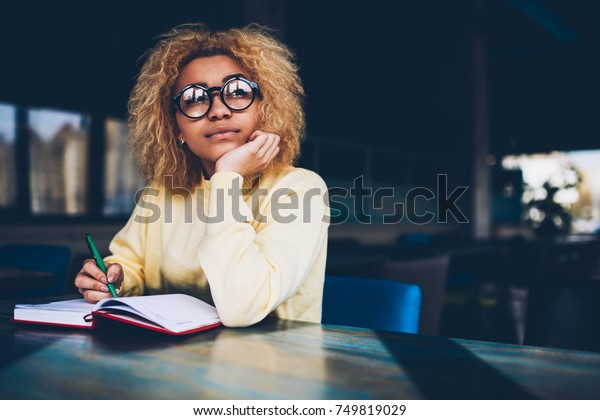 Thoughtful young woman in eyeglasses writing to do list of goals writing in diary in coffee shop, female student dreaming about weekends while making notes in personal organizer planning day