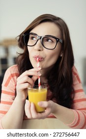 Thoughtful young woman in heavy rimmed glasses sitting sipping orange juice and looking off to the side