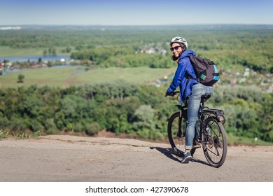 Thoughtful young woman with helmet riding bike in forest