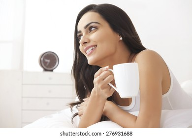 Thoughtful young woman holding coffee cup in bed