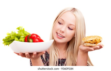 thoughtful young woman holding a hamburger with chicken and plate with vegetables, isolated against white background