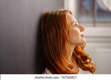 Thoughtful young woman leaning on an interior wall daydreaming looking up with a faraway expression in profile