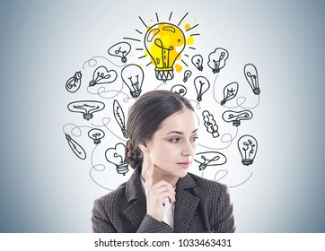 Thoughtful young woman with long dark hair wearing a suit is thinking. She is looking sideways and touching her face with a finger. Yellow light bulbs on a gray wall