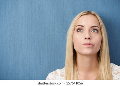 Thoughtful young woman with long straight blond hair standing against a green background with copyspace biting her lip as she stares upwards lost in thought