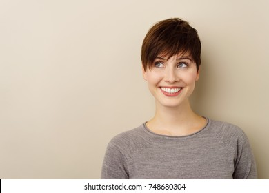 Thoughtful young woman looking up to the side with a happy smile towards blank white copy space