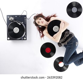 Thoughtful Young Woman Lying on the White Floor with Vinyl Turnaround and Records While Listening to Music, Captured on High Angle View.
