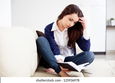Thoughtful young woman reading a book at home
