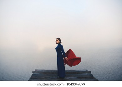 thoughtful young woman with a red shawl scarf stands in the middle of the river in the morning fog, the handkerchief develops in the wind. Beautiful blur background. Fog background. Photo meditation,