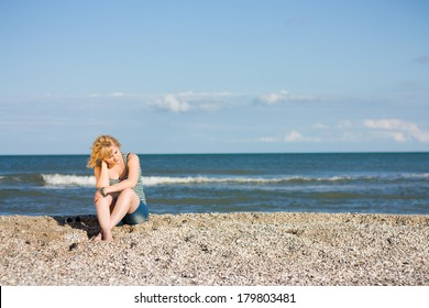 Thoughtful young woman sitting on the beach