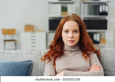 Thoughtful young woman staring intently ahead at the camera with a serious expression and folded arms as she relaxes on a sofa at home