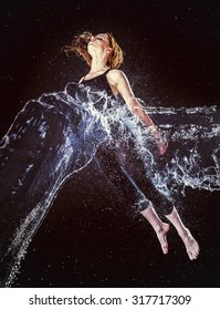 Thoughtful Young Woman in Water Splash Floating in the Air Against Abstract Black Background.