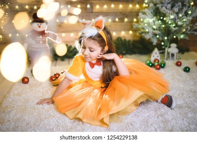 thoughtfulg girl in orange dress at Christmas studio