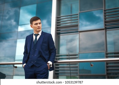 Thoughtfull asian groom in a dark blue suit waiting for his bride against the backdrop of the architecture of the city. concept of a strong successful man