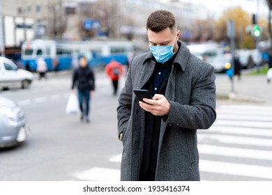 Thoughtfull man in mask standing near crossroad and searching in phone. Coronavirus pandemic in world.