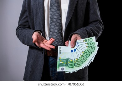 A Thousand Euros. A Man offering 100 euro banknotes.