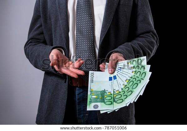 A Thousand Euros. A Man offering 100 euro banknotes.