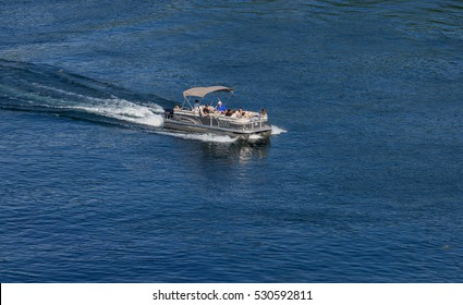 Thousand Islands, Ontario - August 27, 2016: Pontoon boat with a roof moving across the blue water in the Thousand Islands area