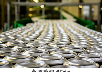 Thousands of beverage aluminum cans on conveyor line at factory. Concept of industrial power and growth